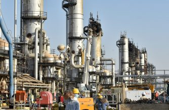 (FILES) This file photo taken on September 20, 2019 shows employees of Aramco oil company working in Saudi Arabia's Abqaiq oil processing plant. - Saudi Aramco shares hit the lowest level since their market debut today, as Gulf bourses were hit by a panicky sell-off amid Iranian vows of retaliation over the US killing of a top general. All seven bourses in the Gulf Cooperation Council (GCC) states closed in the red, on the first trading day since the death of powerful military commander Qasem Soleimani. (Photo by Fayez Nureldine / AFP)