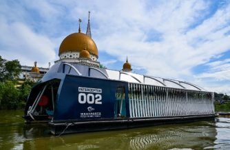 "This picture taken on December 17, 2019 shows the garbage-picking Interceptor seen on the Klang river, in front of a mosque in Klang, on the outskirts of Kuala Lumpur. - Scooping waste from a Malaysian river to stop it reaching the sea, a solar-powered barge named the ""Interceptor"" is the latest weapon in a global battle to rid the world's waters of plastic. (Photo by Mohd RASFAN / AFP)"