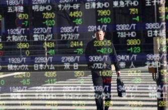 A man is seen reflected as he crosses the street in front of a stock indicator showing share prices of Japanese companies in Tokyo on January 6, 2020. - Tokyo's benchmark Nikkei index plunged nearly two percent on January 6, its first trading day of 2020, in line with the risk aversion across global markets after the US killing of a top Iranian general. (Photo by Behrouz MEHRI / AFP)