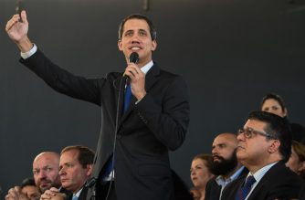 Venezuelan opposition leader Juan Guaido (C) speaks during a press conference, accompanied by opposition lawmakers and supporters, at El Hatillo teather in Caracas, on January 7, 2020. - Venezuelan opposition leader Juan Guaido called Tuesday for three days of protests against President Nicolas Maduro, just hours after he was sworn in for another term as speaker of parliament. (Photo by CRISTIAN HERNANDEZ / AFP)