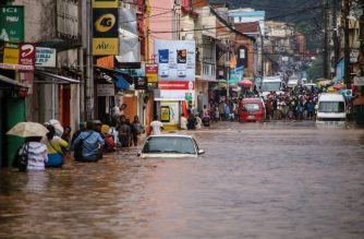 Residents walk through floodwaters past submerged vehicles on a road in Antananarivo on January 8, 2020, after heavy rainfall. (Photo by MAMYRAEL / AFP)