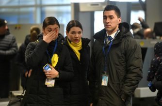 """Members of a plane crew for the Ukraine International Airlines, react at the Boryspil airport outside Kiev on January 11, 2020, as they pay a tribute at a makeshift memorial for the victims of the Boeing 737-800 that crashed outside the Iranian capital Tehran. - Ukraine on Saturday demanded that Iran punish those guilty for the downing of a Ukrainian airliner and compensate victims while praising Tehran for cooperating with the """"objective"""" investigation. (Photo by Sergei SUPINSKY / AFP)"""