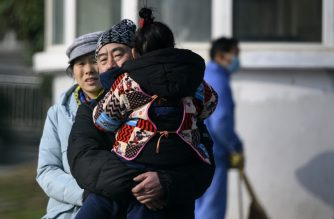 A man holding her daughter leaves the Wuhan Medical Treatment Centre, where a man who died from a respiratory illness was confined, in the city of Wuhan, Hubei province, on January 12, 2020. - A 61-year-old man has become the first person to die in China from a respiratory illness believed caused by a new virus from the same family as SARS, which claimed hundreds of lives more than a decade ago, authorities said. (Photo by NOEL CELIS / AFP)