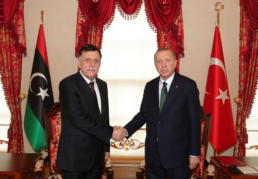 Two diplomats shaking hands in agreement between the Libya and Turkey flag