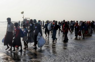 Rohingya people who were arrested at sea in December walk on a beach after being transported by Myanmar authorities to Thalchaung near Sittwe in Rakhine state on January 13, 2020. - 173 Rohingya Muslims fleeing Myanmar were arrested at sea in December by Myanmar's navy and were escorted back to Rakhine state on January 13, authorities said. (Photo by STR / AFP)