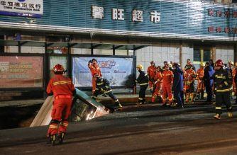 This photo taken on January 13, 2020 shows Chinese rescuers preparing to lift a bus after a road collapse in Xining in China's northwestern Qinghai province. - An enormous sinkhole swallowed passers-by and a public bus in northwest China, reported state media on January 14, injuring fifteen people while another ten are still missing. (Photo by STR / AFP) / China OUT