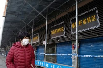 (FILES) In this file photograph taken on January 12, 2020 a woman walks in front of the closed Huanan wholesale seafood market, where health authorities say a man who died from a respiratory illness had purchased goods from, in the city of Wuhan, Hubei province. - A second person has died in China from a mystery virus that has stricken dozens and appeared in two other Asian countries, officials said. (Photo by NOEL CELIS / AFP)