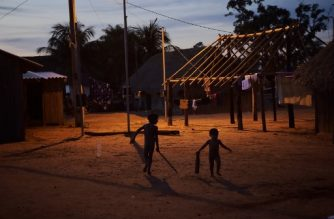 Indigenous children play at dusk after a speech by his leader Cacique Raoni Metuktire (not depicted) of the Kayapo tribe, in Piaracu village, near Sao Jose do Xingu, Mato Grosso state, Brazil, on January 17, 2020. - Dozens of Amazon indigenous leaders have gathered in the heart of the threatened rainforest to form an alliance against Brazilian President Jair Bolsonaro's environmental policy and his threats to throw their homelands open to mining concerns. (Photo by CARL DE SOUZA / AFP)