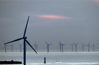 (FILES) In this file photo taken on May 14, 2019 New Brighton lighthouse is pictured at sunset, in New Brighton, at the mouth of the river Mersey, in north-west England on May 14, 2019, with the Burbo Bank Offshore Wind Farm visible on the horizon. - Britain, a global leader in offshore wind energy, plans to make the sector one of the pillars of its transition to carbon neutrality in the coming decades. The country aims to quadruple its offshore electricity production capacity by 2030 by utilising the windswept North Sea and a favourable policy environment. (Photo by Paul ELLIS / AFP)