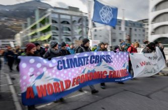 People hold a banner as they take part in a gathering called by climate activists prior to the start of a march to Davos ahead of the World Economic Forum in January 19, 2020 in Landquart. (Photo by FABRICE COFFRINI / AFP)