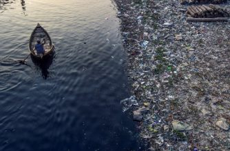 A man paddles on a boat as plastic bags float on the water surface of the Buriganga river in Dhaka on January 21, 2020. - Bangladesh's high court has ordered the shutdown of 231 factories that have contributed to Dhaka's main river becoming one of the world's most polluted, a lawyer said on January 21. (Photo by MUNIR UZ ZAMAN / AFP)