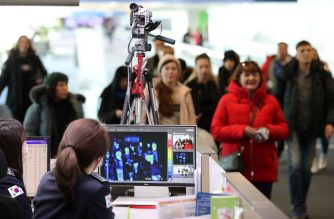 In this picture taken on January 21, 2020 a quarantine officer (bottom) monitors a thermal scanner as passengers from an international flight arrive at Incheon international airport, west of Seoul. - South Korea on January 20 confirmed its first case of the SARS-like virus that is spreading in China, as concerns mount about a wider outbreak. (Photo by STR / various sources / AFP) / South Korea OUT