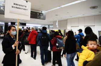 Passengers who arrived on one of the last flights from the Chinese city of Wuhan walk through a health screening station at Narita airport in Chiba prefecture, outside Tokyo, on January 23, 2020, as countries screen for anyone showing symptoms of a SARS-like virus which has killed at least 17 people and infected over 500. - China banned trains and planes from leaving Wuhan at the centre of a virus outbreak on January 23, seeking to seal off its 11 million people to contain the contagious disease that has claimed 17 lives, infected hundreds and spread to other countries. (Photo by CHARLY TRIBALLEAU / AFP)