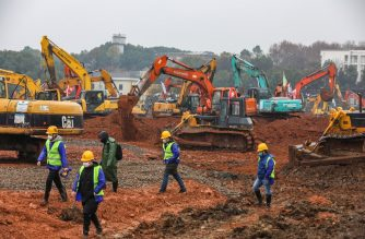 Employees work at a construction site of a hospital to treat patients during a virus outbreak in Wuhan in China's central Hubei province on January 24, 2020. - China is rushing to build a new hospital in a staggering 10 days to treat patients at the epicentre of a deadly virus outbreak that has stricken hundreds of people, state media reported on January 24. (Photo by STR / AFP) / China OUT