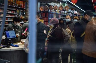 People wearing protective facemasks queue up at the check-out counter at a store in Wuhan on January 26, 2020, a city at the epicentre of a viral outbreak that has killed at least 56 people and infected nearly 2,000. - China on January 26 expanded drastic travel restrictions to contain the viral contagion, as the United States and France prepared to evacuate their citizens from the quarantined city at the outbreak's epicentre. (Photo by Hector RETAMAL / AFP)