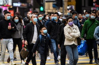 Pedestrians wearing face masks cross a road during a Lunar New Year of the Rat public holiday in Hong Kong on January 27, 2020, as a preventative measure following a coronavirus outbreak which began in the Chinese city of Wuhan. (Photo by Anthony WALLACE / AFP)
