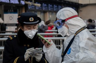 A security personnel wearing protective clothing to help stop the spread of a deadly virus which began in Wuhan, talks with a subway staff (L) wearing a mask at a subway station entrance in Beijing on January 27, 2020. - China on January 27 extended its biggest national holiday to buy time in the fight against a viral epidemic and neighbouring Mongolia closed its border, after the death toll spiked to 81 despite unprecedented quarantine measures. (Photo by NICOLAS ASFOURI / AFP)