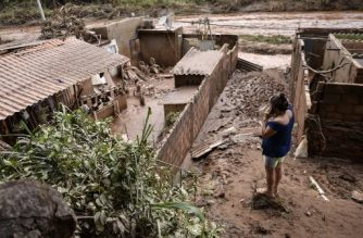 A woman stares at damages caused by the overflowing of Das Velhas River following torrential rains, in Sabara, in the metropolitan region of Belo Horizonte, Minas Gerais state, Brazil, on January 27, 2020. - The death toll from days of intense storms and flooding in southeastern Brazil has risen to 44, while the number of injured stands at 12 and that of the missing was lowered from 25 to 19, local Civil Defense officials said. (Photo by DOUGLAS MAGNO / AFP)