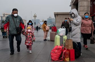 People wearing protective masks to help stop the spread of a deadly virus which began in Wuhan, stand next to their suitcases at the Beijing railway station in Beijing on January 27, 2020. - China on January 27 extended its biggest national holiday to buy time in the fight against a viral epidemic and neighbouring Mongolia closed its border, after the death toll spiked to 81 despite unprecedented quarantine measures. (Photo by NICOLAS ASFOURI / AFP)