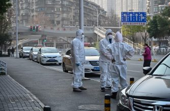 This photo taken on January 30, 2020 shows officials in protective suits gathered on a street after an elderly man wearing a facemask (not pictured) collapsed and died on the pavement near a hospital in Wuhan. - AFP journalists saw the body on January 30, not long before an emergency vehicle arrived carrying police and medical staff in full-body protective suits. The World Health Organization declared a global emergency over the new coronavirus, as China reported on January 31 the death toll had climbed to 213 with nearly 10,000 infections. (Photo by Hector RETAMAL / AFP) / TO GO WITH China-health-virus-death,SCENE by Leo RAMIREZ and Sebastien RICCI