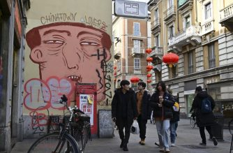 "People pass by a mural depicting a chinese face in via Paolo Sarpi, the commercial street of the chinese district of Milan on January 30, 2020. - Several well-known figures in the Chinese community in Italy on January 30, 2020 denounced ""Discrimination without distinction"" and ""latent racism"" from Italians frightened by the coronavirus epidemic and the risks of contagion. (Photo by Miguel MEDINA / AFP)"