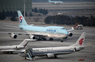 An airplane (C) carrying South Korean citizens repatriated from the Chinese city of Wuhan lands at Gimpo airport in Seoul on January 31, 2020. - The first evacuation plane carrying 367 South Koreans from the coronavirus-hit Chinese city of Wuhan arrived in Seoul on January 31, Yonhap news agency reported. (Photo by Jung Yeon-je / AFP)