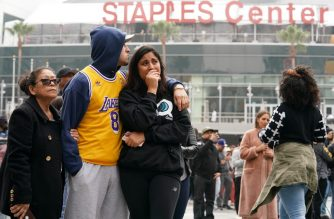 LOS ANGELES, CALIFORNIA - JANUARY 26: (L-R) Los Angeles Lakers fans Lilian Gamez, Gabriel Gamez and Angelica Rodriguez mourn the death of retired NBA star Kobe Bryant outside the Staples Center prior to the 62nd Annual Grammy Awards on January 26, 2020 in Los Angeles, California. Bryant, 41, died today in a helicopter crash in near Calabasas, California.   Rachel Luna/Getty Images/AFP