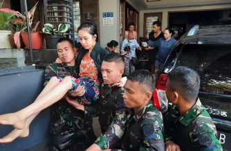 Indonesian soldiers evacuate a woman who is recovering from surgery, from her flooded house in Tangerang, Banten province, on January 2, 2020. (Photo by D'MARTIAZ / AFP)