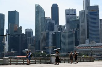 (FILE) People walk along the pier at Marina Bay in Singapore on October 11, 2019. (Photo by ROSLAN RAHMAN / AFP)