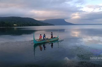 In this screen grab of the video taken by Eagle News Service correspondent Ghadzs Rodelas, boaters brave the seemingly serene Taal Lake to go back to Taal volcano island on Tuesday morning, Jan. 14, 2020 despite the continuous eruption of the volcano.  (Eagle News Service)