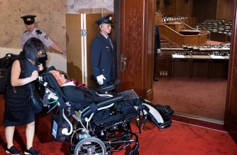 Wheelchair-bound Japanese lawmaker Yasuhiko Funago enters the Upper House plenary hall to attend a session at the Diet in Tokyo on August 1, 2019. - Two lawmakers with serious paralysis took their seats in Japan's upper house on August 1 to cheers from supporters, marking the first time people with severe disabilities have served in the body. (Photo by Kazuhiro NOGI / AFP)