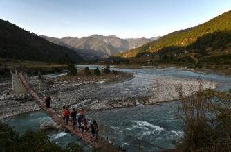 This photo taken on December 6, 2019 shows tourists walking on a suspension bridge over the Puna Tsang Chhu river in Punakha province in Bhutan. (Photo by Lillian SUWANRUMPHA / AFP)