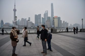 A man wearing a protective mask takes a pictures on the promenade of the Bund along the Huangpu River in Shanghai on January 21, 2020. - The number of people in China infected by a new SARS-like virus jumped to 291 on January 21, according to authorities. There have been nearly 80 new confirmed cases of the virus that has so far killed four people, with over 900 still under medical observation, said the National Health Commission. (Photo by HECTOR RETAMAL / AFP)