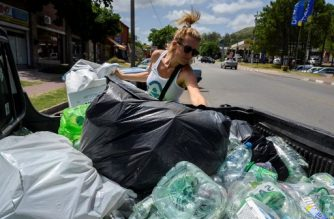 Uruguayan Nicole Wyaux, founder of Plasticoin, collects plastic from a Plasticoin collection center at San Francisco beach in Priapolis, Uruguay, on January 22, 2020. - In Piriapolis, an historic seaside resort by the Uruguayan coast, an entrepreneurship seeks to eliminate plastic on the beaches by encouraging those who collect, clean and compact it, with a payment in a virtual currency that allows people to buy and have discounts on certain products. (Photo by Pablo PORCIUNCULA BRUNE / AFP)