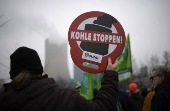 """A supporter of Fridays for Future movement holds a placard reading """"stop coal"""" during a demonstration against the commissioning of the coal-fired power plant Datteln 4 in Datteln, western Germany on January 24, 2020. (Photo by INA FASSBENDER / AFP)"""