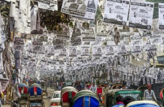 In this photograph taken on January 29, 2020, commuters make their way on a street adorned with election posters laminated with plastic in Dhaka.  - Dhaka is awash with millions of plastic-laminated campaign posters ahead of elections in the Bangladeshi capital, and environmentalists are up in arms. (Photo by Munir UZ ZAMAN / AFP) / To go with story 'BANGLADESH-ENVIRONMENT-WASTE-ELECTION'