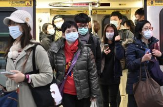 Mask-clad commuters get off a train at a Mass Rapid Transit (MRT) stop in Taipei following the Lunar New Year holidays on January 30, 2020. - Taiwan has uncovered eight cases of the virus similar to the SARS pathogen so far, including two female Chinese nationals in their 70s who arrived in the country as part of a tour group, as the death toll January 30 from the epidemic originating from Wuhan in China leapt to 170, with 7,892 confirmed infections. (Photo by Sam Yeh / AFP)