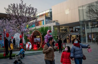 "A family (R) wearing a protective facemasks walk outside an Apple store (back) in Beijing on January 30, 2020. - The World Health Organization, which initially downplayed the severity of a disease that has now killed 170 nationwide, warned all governments to be ""on alert"" as it weighed whether to declare a global health emergency. (Photo by NICOLAS ASFOURI / AFP)"