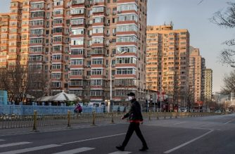 A man wearing a protective mask walks along an empty street in Beijing on January 31, 2020, following a SARS-like virus outbreak which began in the Chinese city of Wuhan. - The World Health Organization declared an international emergency after China's National Health Commission said nearly 8,000 people had been infected, and about 100 cases were reported outside China. (Photo by NICOLAS ASFOURI / AFP)