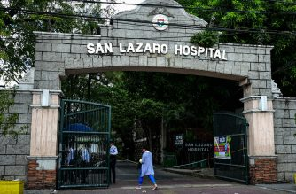 People wearing face masks walk past the main gates of the San Lazaro Hospital in Manila on February 2, 2020. - The Philippines reported the first death outside of China from a new coronavirus, deepening global fears about an epidemic that has claimed more than 300 lives. (Photo by Maria TAN / AFP)