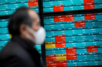 A pedestrian wearing a face mask walks past a stock indicator displaying share prices of the Tokyo Stock Exchange in Tokyo on February 3, 2020. - Tokyo stocks dropped on February 3 as the Chinese market plunged after investors returned from an extended holiday during which the new coronavirus outbreak drove down the global market. (Photo by Behrouz MEHRI / AFP)