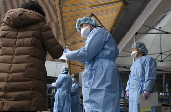 Hospital officials wearing protective gear guide visitors to help prevent the spread of the SARS-like virus, at the entrance of a hospital in Seoul on February 4, 2020. - South Korea has confirmed 16 cases of the SARS-like virus so far and placed nearly 130 people in quarantine for detailed checks amid growing public alarm. (Photo by Jung Yeon-je / AFP)