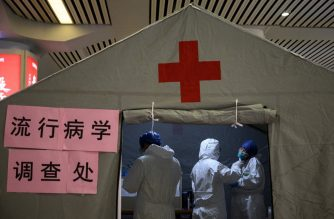 """Health personnel work at their medical tent erected at the Hangzhou East Railway station in Hangzhou, some 175 kilometres (110 miles) southwest of Shanghai on February 5, 2020. - The world has a """"window of opportunity"""" to halt the spread of a deadly new virus, global health experts said, as the number of people infected in China jumped to 24,000 and millions more were ordered to stay indoors. (Photo by NOEL CELIS / AFP)"""