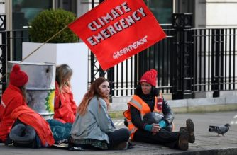 Greenpeace activists sit chained into oil barrels as they protest outside the headquarters of oil giant BP in London on February 5, 2020, on the day that the company's new  was set to take up his role. - Activists from Greenpeace on Wednesday blocked the headquarters of BP in London with solar panels and mock barrels of crude to mark the first day of the oil giant's new CEO, Bernard Looney. (Photo by DANIEL LEAL-OLIVAS / AFP)