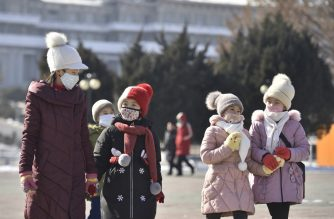 In this photo taken on February 6, 2020, people wearing face masks walk in Pyongyang. - At least 31,000 people have been infected and more than 630 killed by the virus following the outbreak which began in the Chinese city of Wuhan, which has spread to two dozen countries. (Photo by Kim Won-Jin / AFP)