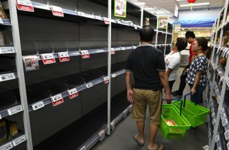 People look at the empty shelves at a local supermarket in Singapore after panic buying swept through the city after the government raised the alert level for a deadly novel coronavirus in Singapore on February 8, 2020 - Anxious Singapore shoppers formed long lines at grocery stores and cleared the shelves of essential items, after the city-state raised its alert level over China's coronavirus outbreak. (Photo by Roslan RAHMAN / AFP)