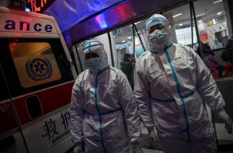 (FILES) This file photo taken on January 25, 2020 shows medical staff members wearing protective clothing to help stop the spread of the deadly COVID-19 coronavirus which began in the city, walking at the Wuhan Red Cross Hospital in Wuhan. - Doctors on the frontline of China's new coronavirus epidemic are facing a daunting task: treat an ever-growing number of infected patients and risk getting infected themselves due to a drastic shortage of masks and other protective equipment. (Photo by Hector RETAMAL / AFP) / TO GO WITH China-health-virus-hospital,FOCUS by Eva Xiao and Ludovic Ehret