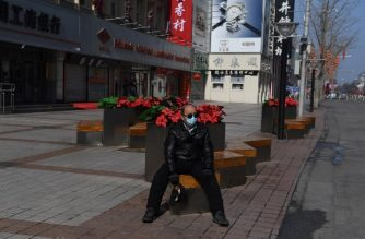 A man wears a protective face mask as he sits in the normally bustling Wangfujing shopping street in central Beijing on February 10, 2020. - As the novel coronavirus virus claims more lives and infects thousands of people every day, it is also taking a toll on the country's small businesses that rely on spending from China's growing middle-class. (Photo by GREG BAKER / AFP)