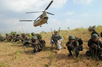 (FILES) This file photo taken on April 20, 2015 shows Philippine soldiers and a US Army soldier from the 2nd Stryker Brigade Combat unit of the 5th Infantry Division based in Hawaii taking their positions after disembarking from a C-47 Chinook helicopter during an air assault exercise inside the military training camp at Fort Magsaysay in Nueva Ecija province. - The Philippines told the US on February 11, 2020 it was quitting a pact key to their historical military alliance, which triggers a six-month countdown to the deal's termination, Manila said. (Photo by TED ALJIBE / AFP)