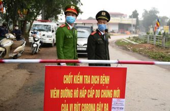 Vietnamese police wearing protective facemasks amid concerns of the COVID-19 coronavirus outbreak stand guard at a checkpoint in Son Loi commune in Vinh Phuc province on February 13, 2020. (Photo by Nhac NGUYEN / AFP)